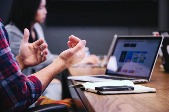 Ahşap bir masanın üzerindeki dizüstü bilgisayar ve bir çift el