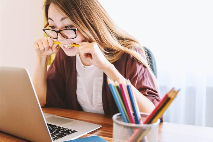Dizüstü bilgisayar karşısında sinirle kalemi ısıran kadın