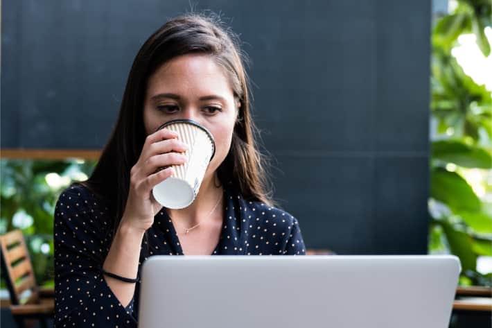 Dizüstü bilgisayar kullanırken kahve içen kadın